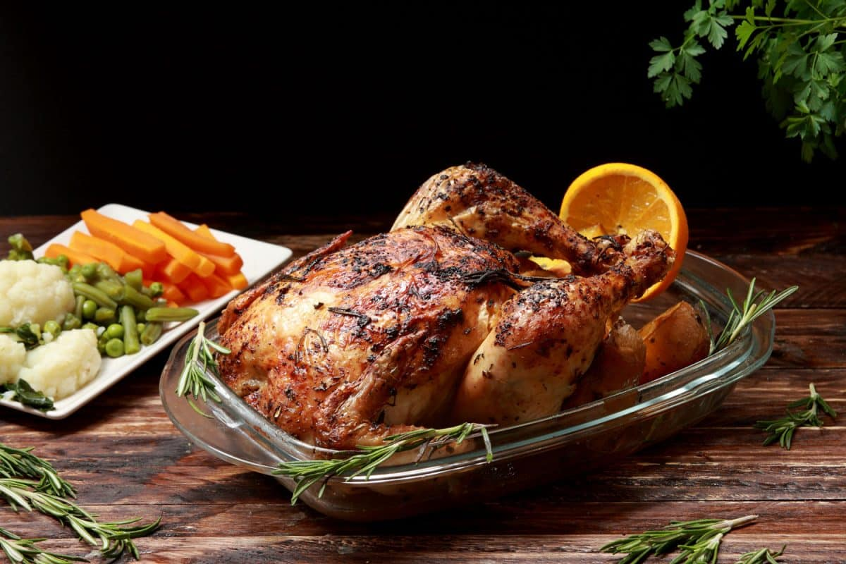 Traditional English Roast Chicken marinated with Herbs and Spices served with Roast Potatoes and Vegetables as a side dish roasted in the oven, Traditional English Roast Chicken marinated with Herbs and Spices served with Roast Potatoes and Vegetables as a side dish