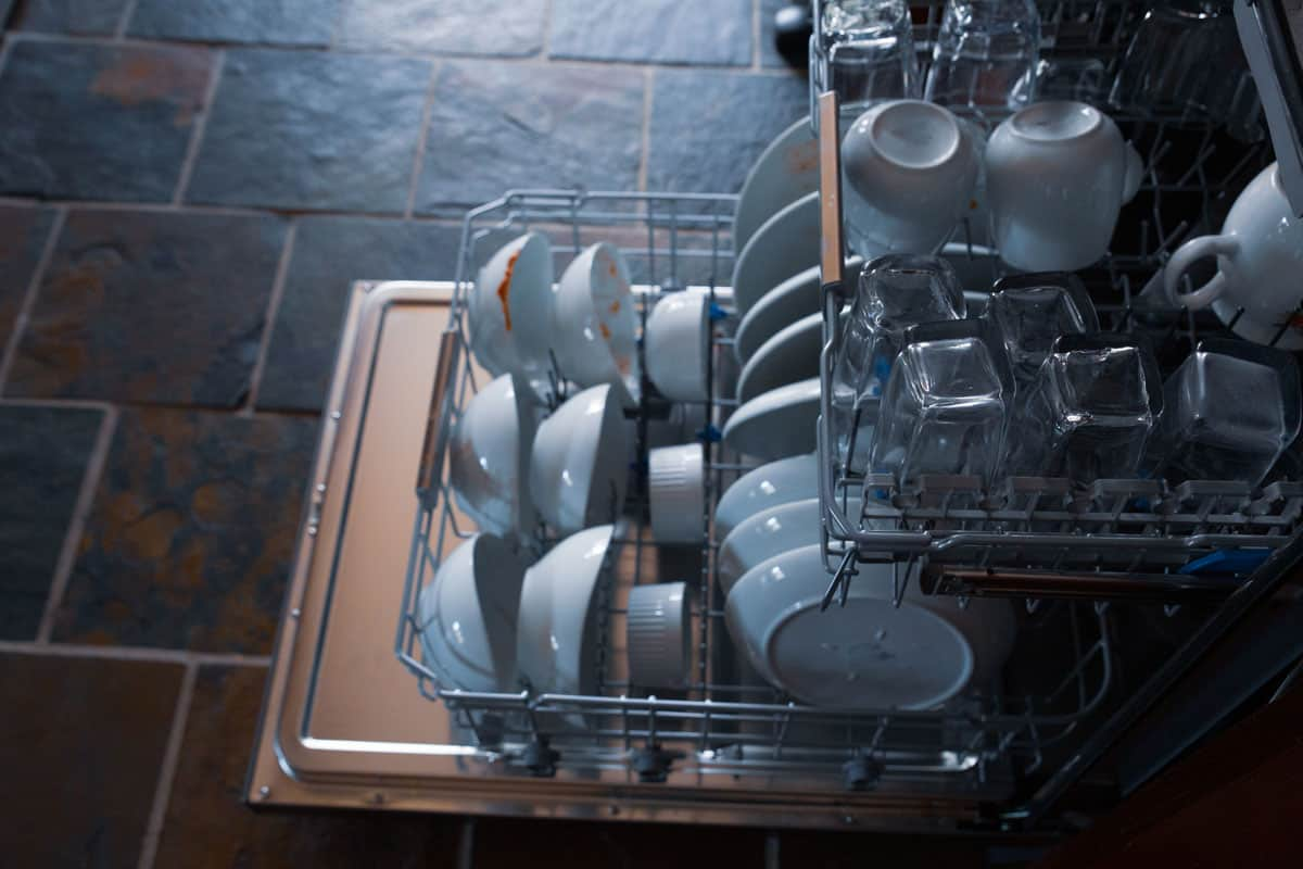 Unwashed dishes glass cups and coffee mugs on a dishwasher