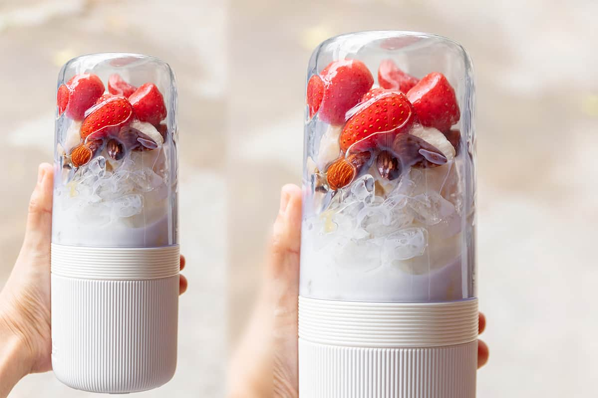 Woman hand holding portable blender with healthy fruits; getting ready for making a smoothie. Fresh strawberry, banana, almond, honey and milk with ice; healthy and fresh concept, featured, Are Blender Bottles Dishwasher-Safe?