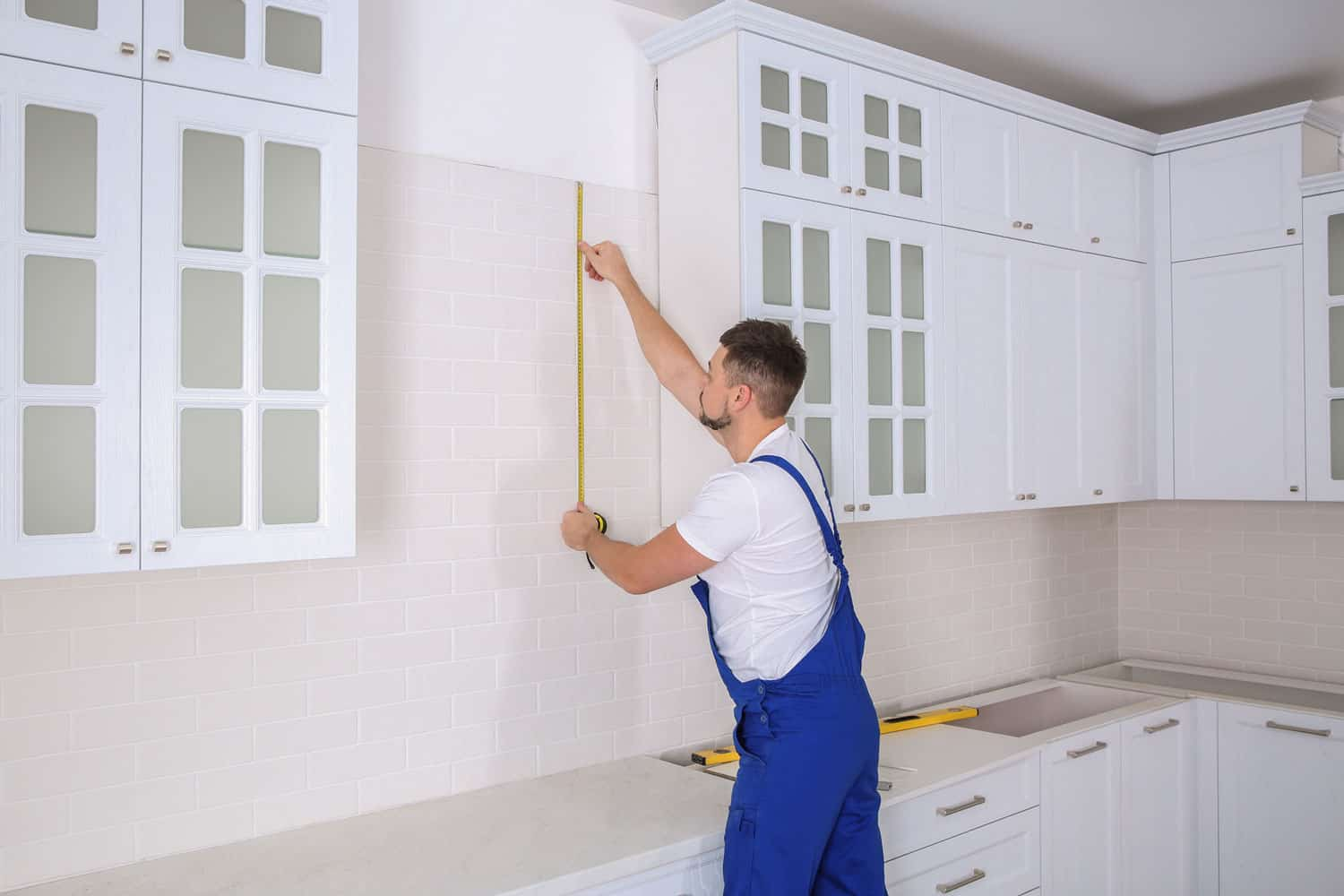 Worker using measuring tape while installing new furniture in kitchen