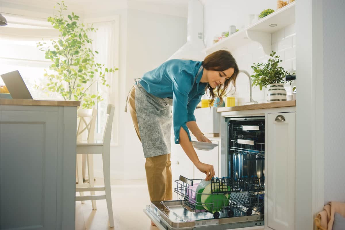 Woman wearing apron loading soiled dishes in a dishwasher in bright kitchen, How To Clean Bosch Dishwasher [5 Steps]