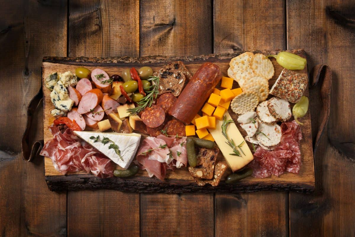 A charcuterie board with lots of different delicacies on it placed on a scorched wooden table, What Kind of Wood is Used for Cheese and Charcuterie Board?