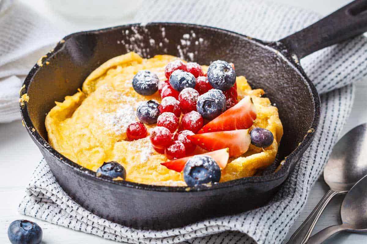 A Dutch baby pancake with berries in a cast-iron pan, How To Keep Pancakes From Sticking To The Pan