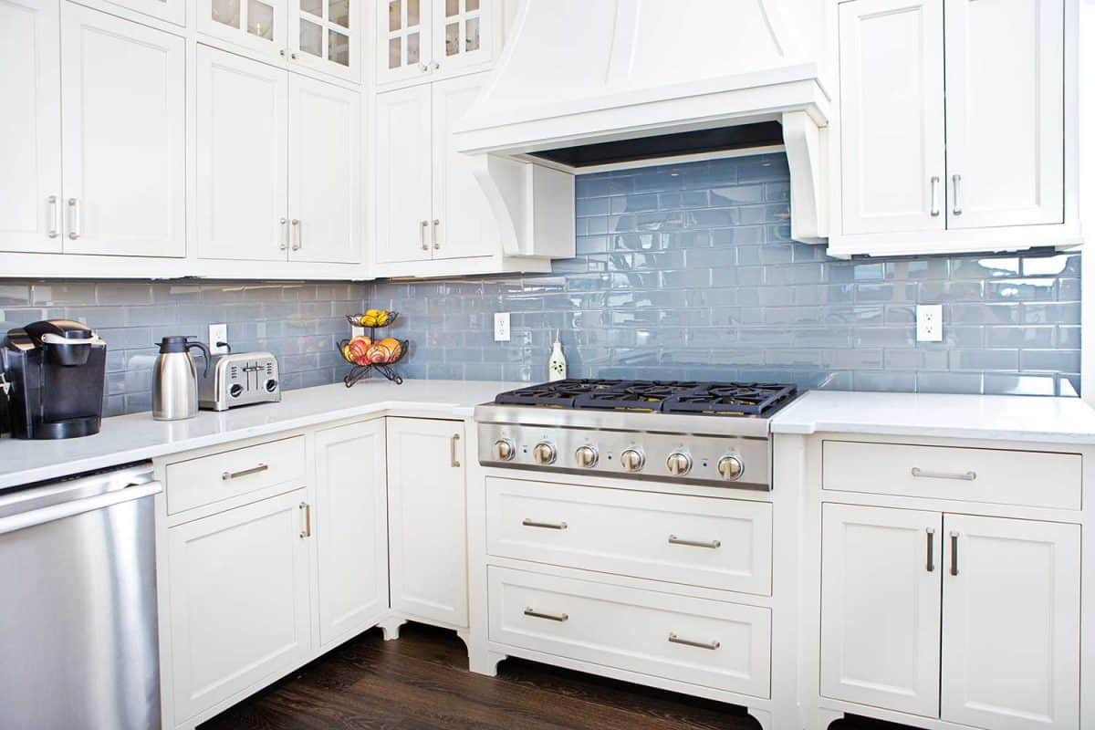A contemporary home kitchen with stainless steel appliances and painted white cabinets