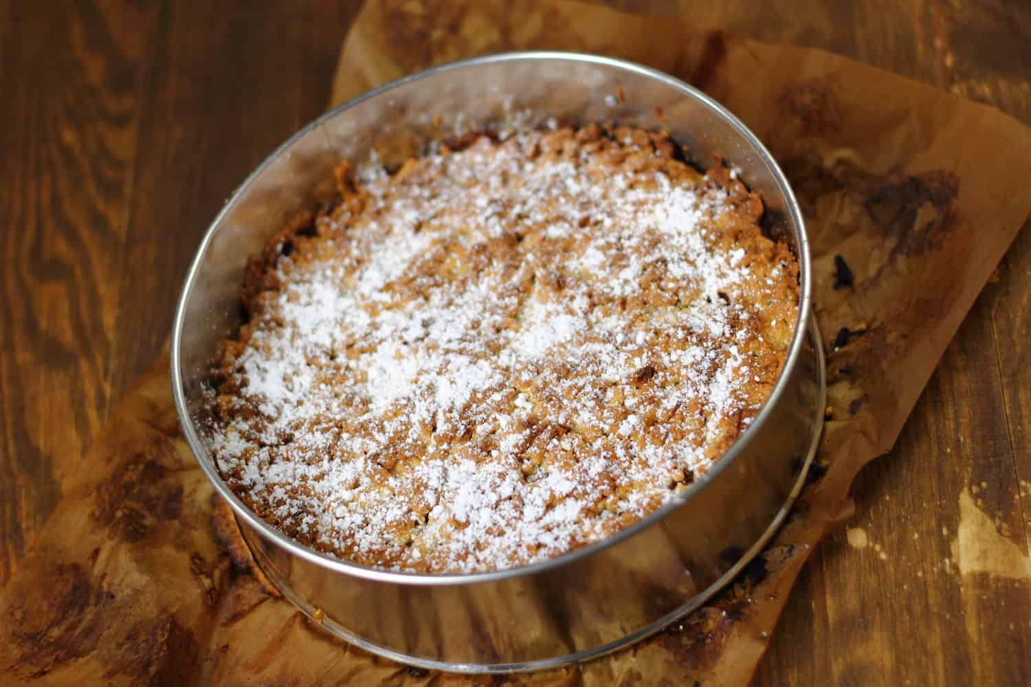 A freshly baked apple pie sprinkled with powdered white sugar