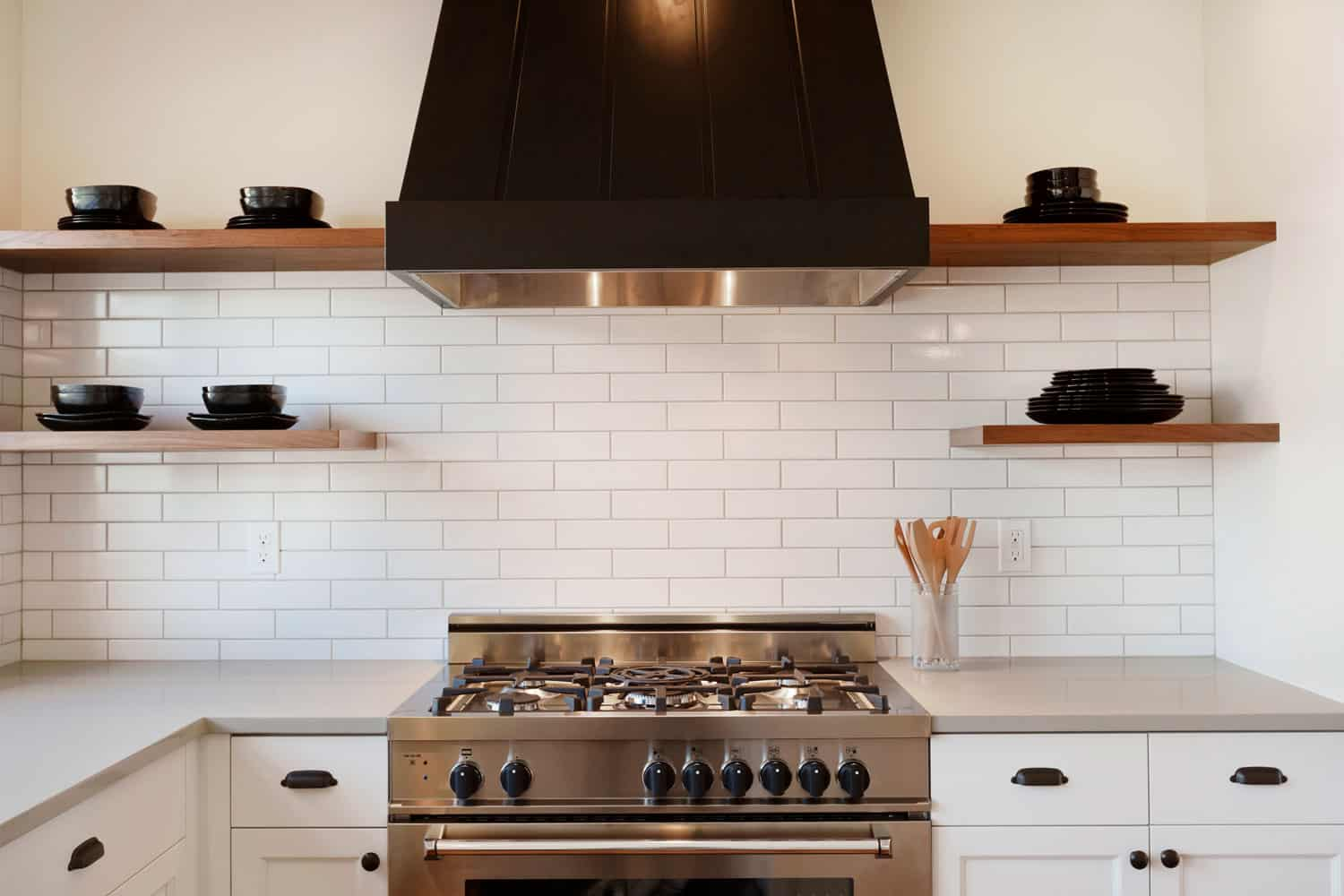 A kitchen stove and hood inside a modern kitchen
