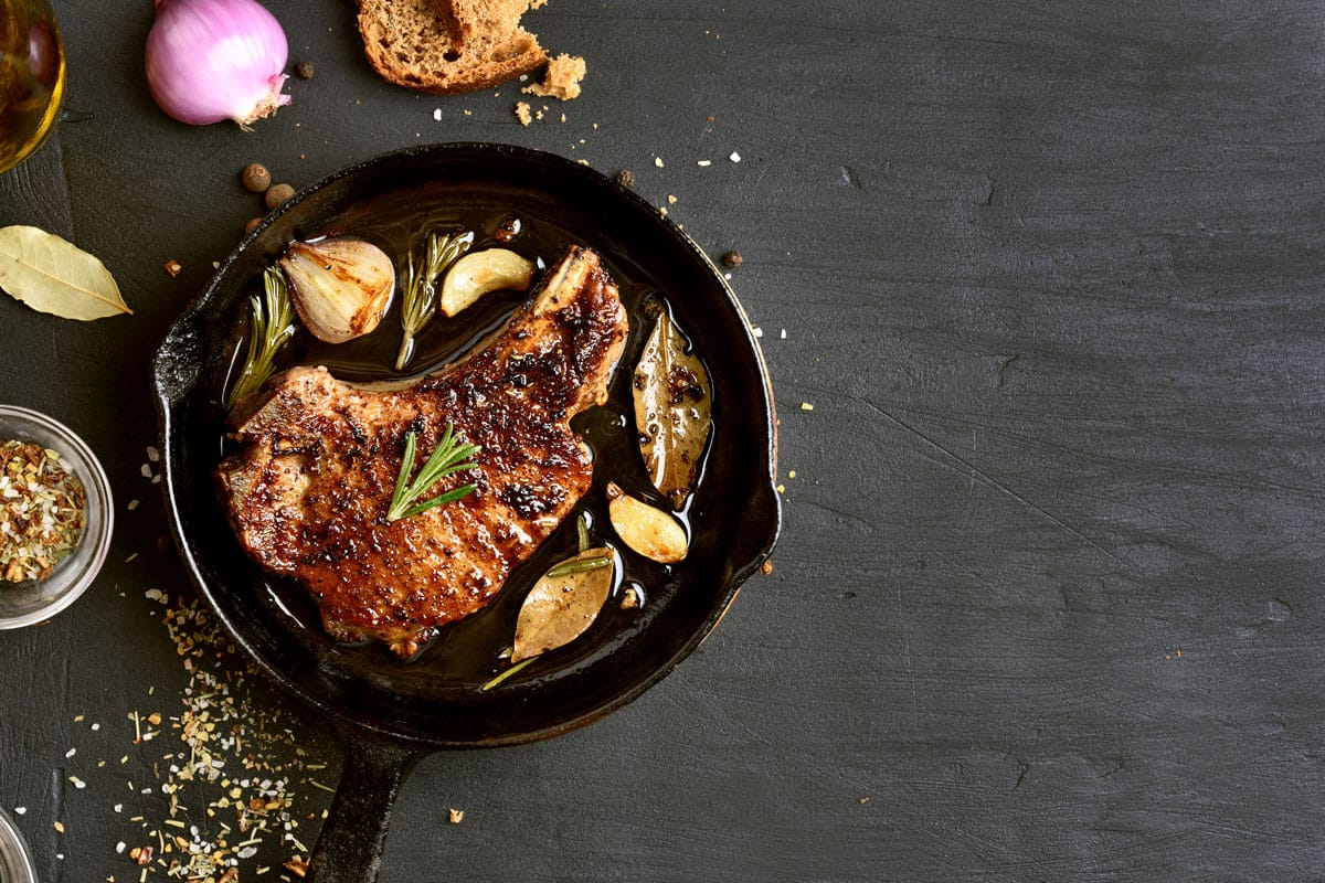 A skillet with a search steak with oregano, bay leaves, and garlic placed on a gray table, How Often Do You Season A Cast Iron Pan?