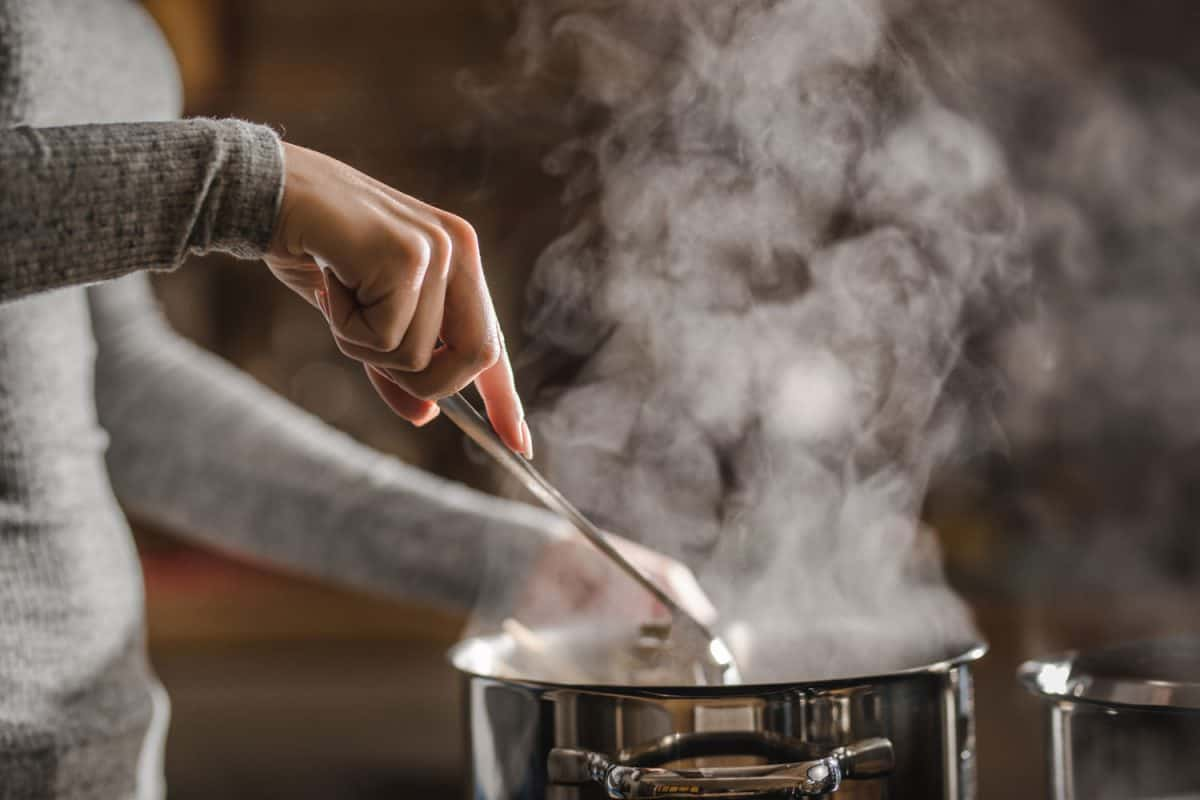 A woman holding a spatula and stirring her cooking on a pot, Is It Bad To Eat Straight Out Of The Pot?