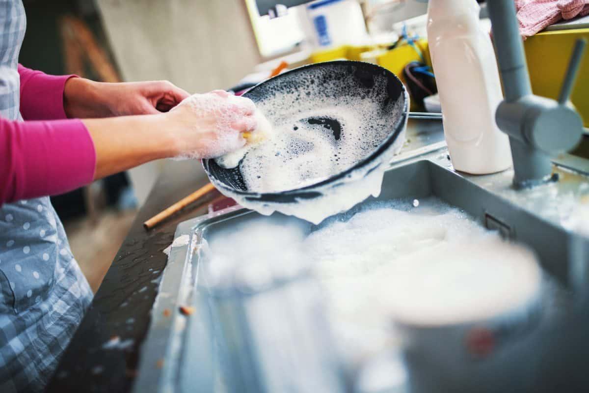 A woman washing a newly used frying pan, How Often Should You Wash A Frying Pan?