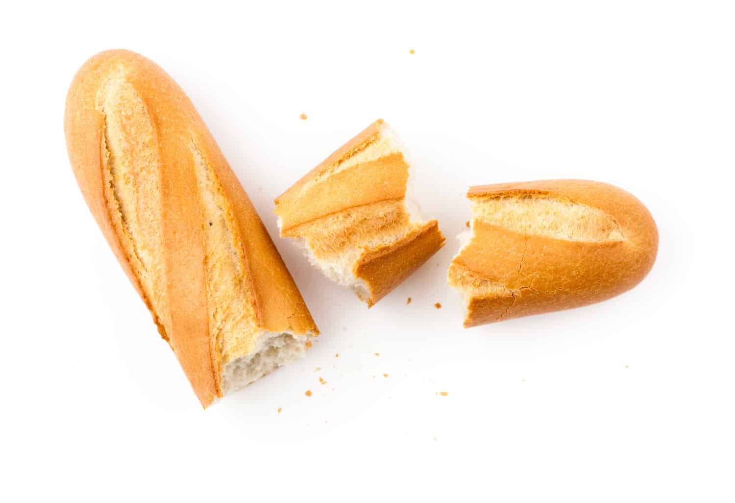 Baguette isolated on white, broken in pieces, crusty french bread