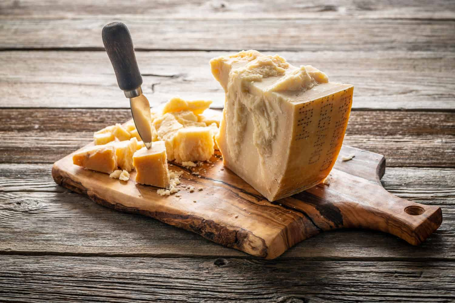 Old Cheddar cheese, irregular shaped big and small pieces, placed on a wooden cheeseboard
