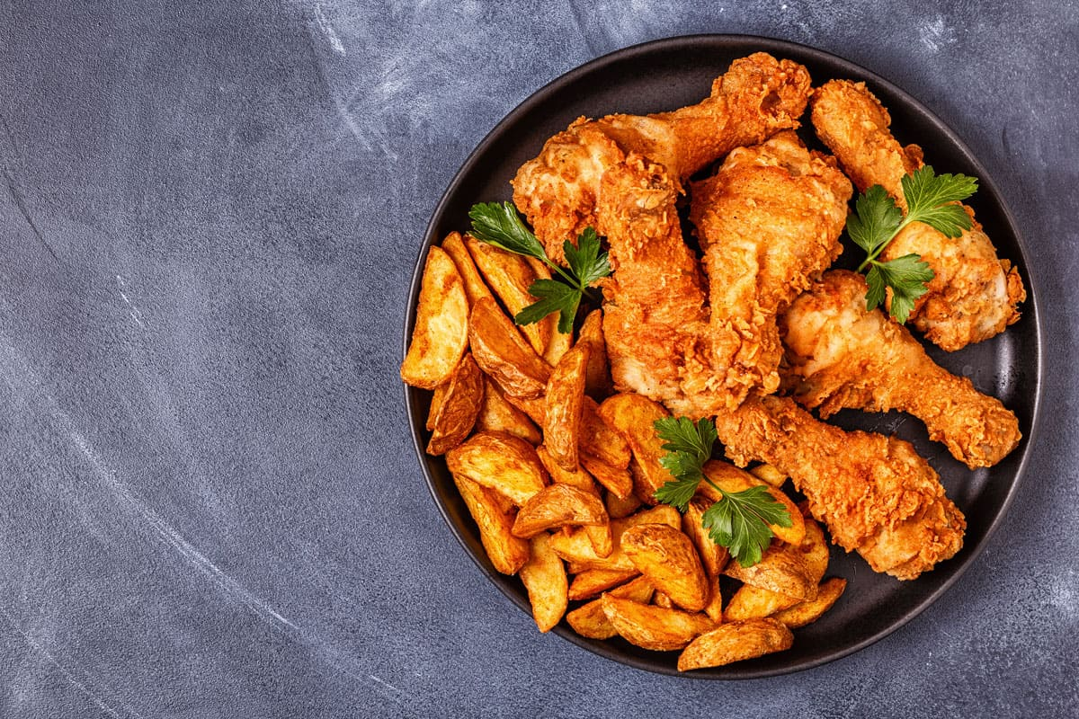 Golden brown deep fried chicken with fried potatoes on the side, What is the Best Pot to Fry Chicken? [3 Great Options!]
