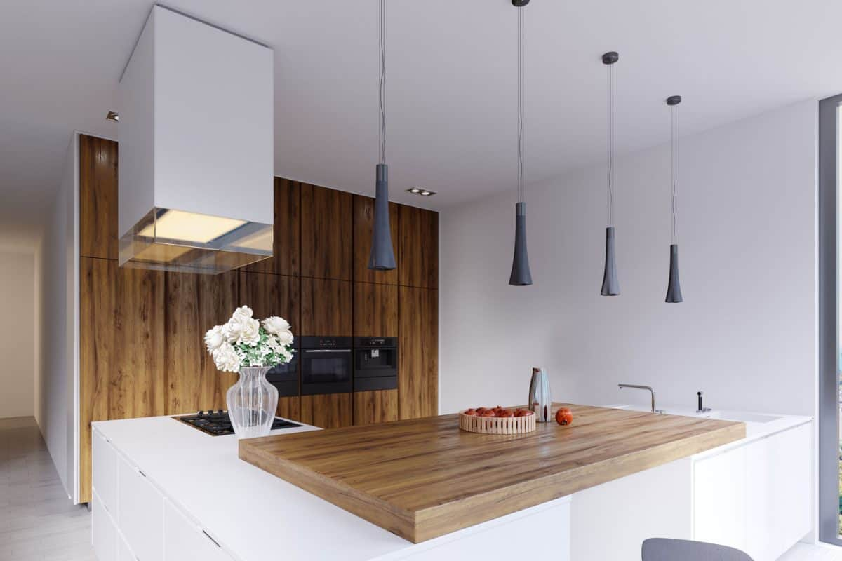 Gorgeous minimalist themed with a wooden breakfast bar with dangling lamps, a freestanding kitchen range, and wooden paneled kitchen cabinets with an oven, Slide In Vs Freestanding Range - Which Should You Choose?