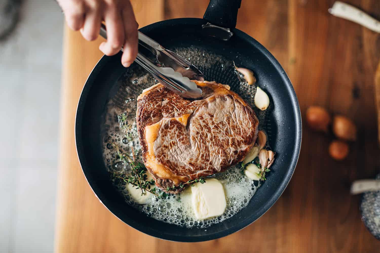 Overhead shot of chef preparing ribeye steak with butter, thyme and garlic. Keto diet.