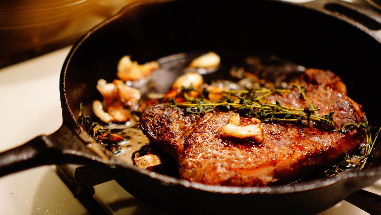 Seasoned ribeye steak on a cast iron pan