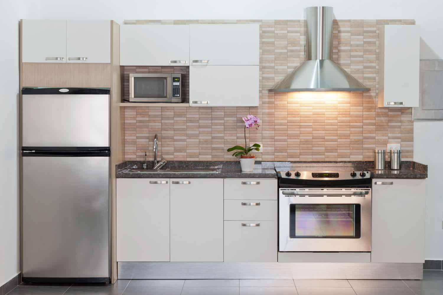 Small modern contemporary kitchen with an oven, stainless steel hood, and white color paneled kitchen cabinets