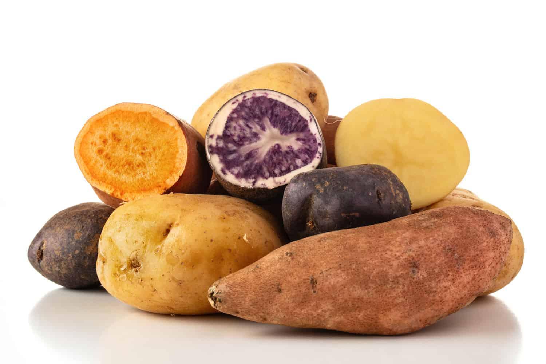 Sweet potatoes, new potatoes, and purple potatoes on a white background