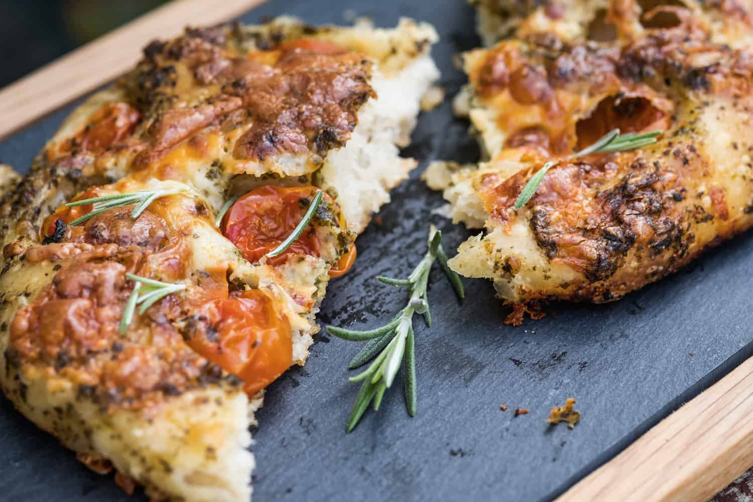 Close up of a hand made focaccia bread topped with cherry tomatoes, pesto, cheese and herbs served on a slate serving platter