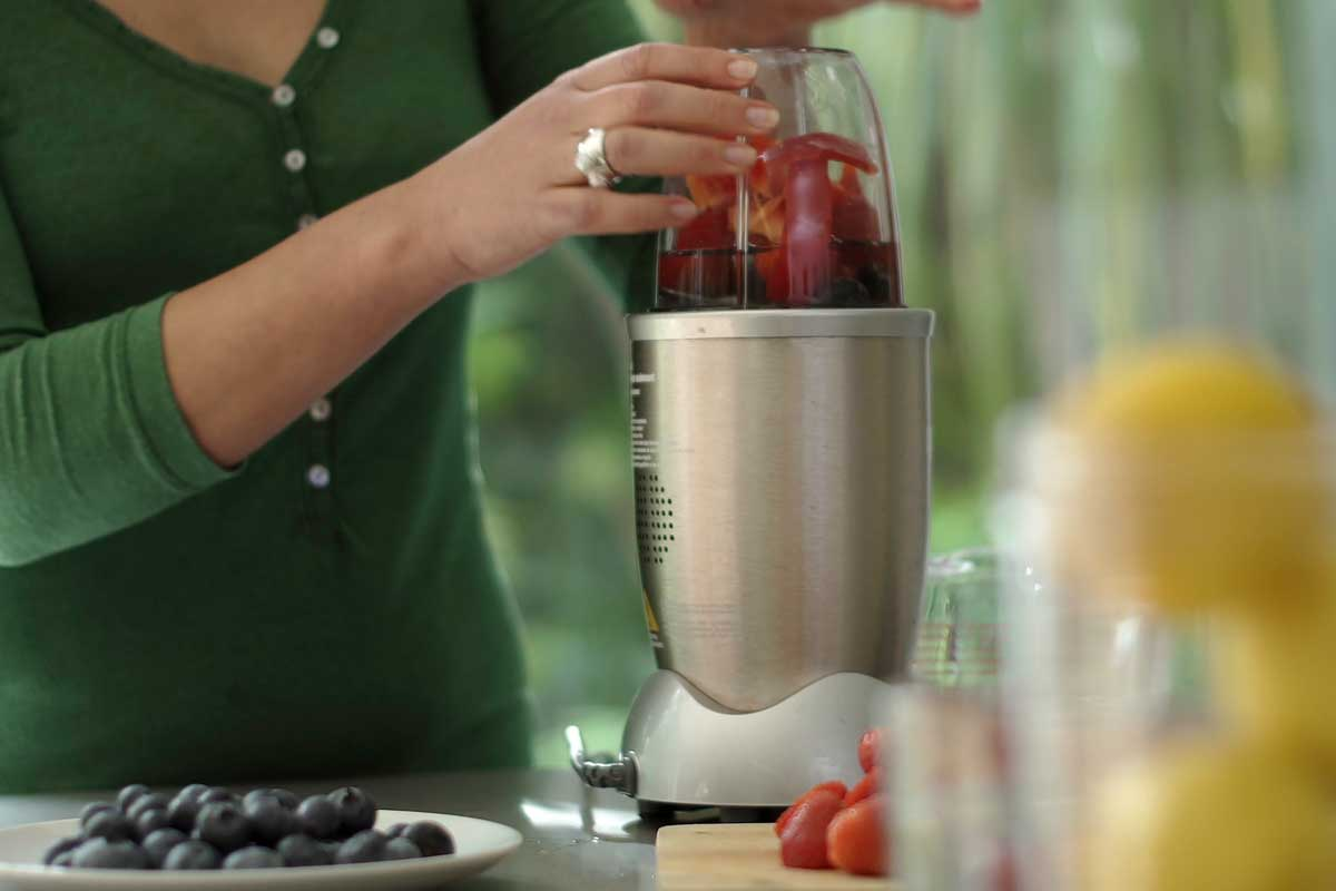 Woman making a fruit smoothie drink using a high speed blender after loading it with fruit, Can You Put Ice In A Nutribullet?