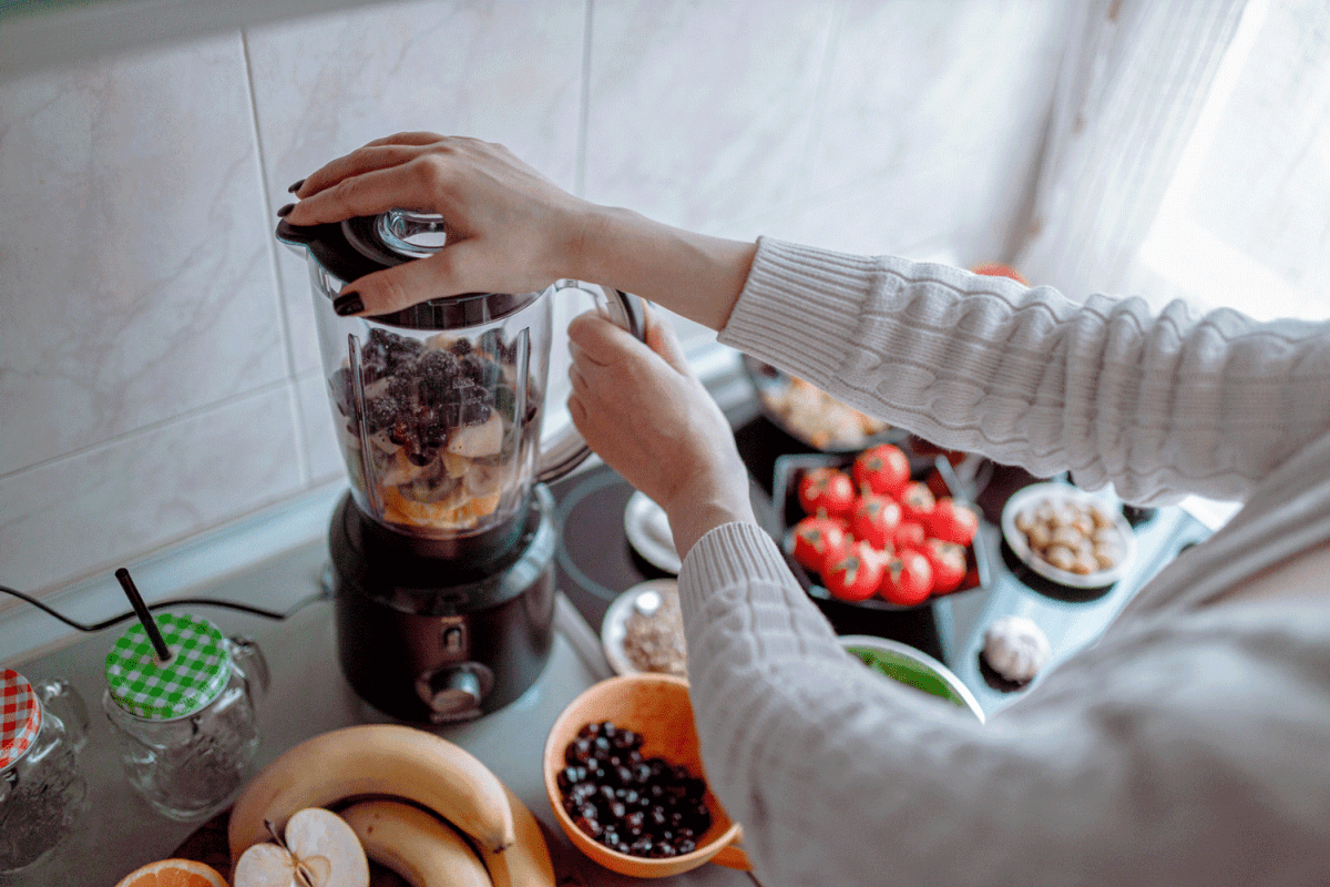 Woman making healthy and tasty smoothies from various fruits and vegetables in the electric blender in the kitchen at home, Ninja Blender Not Working - What To Do?