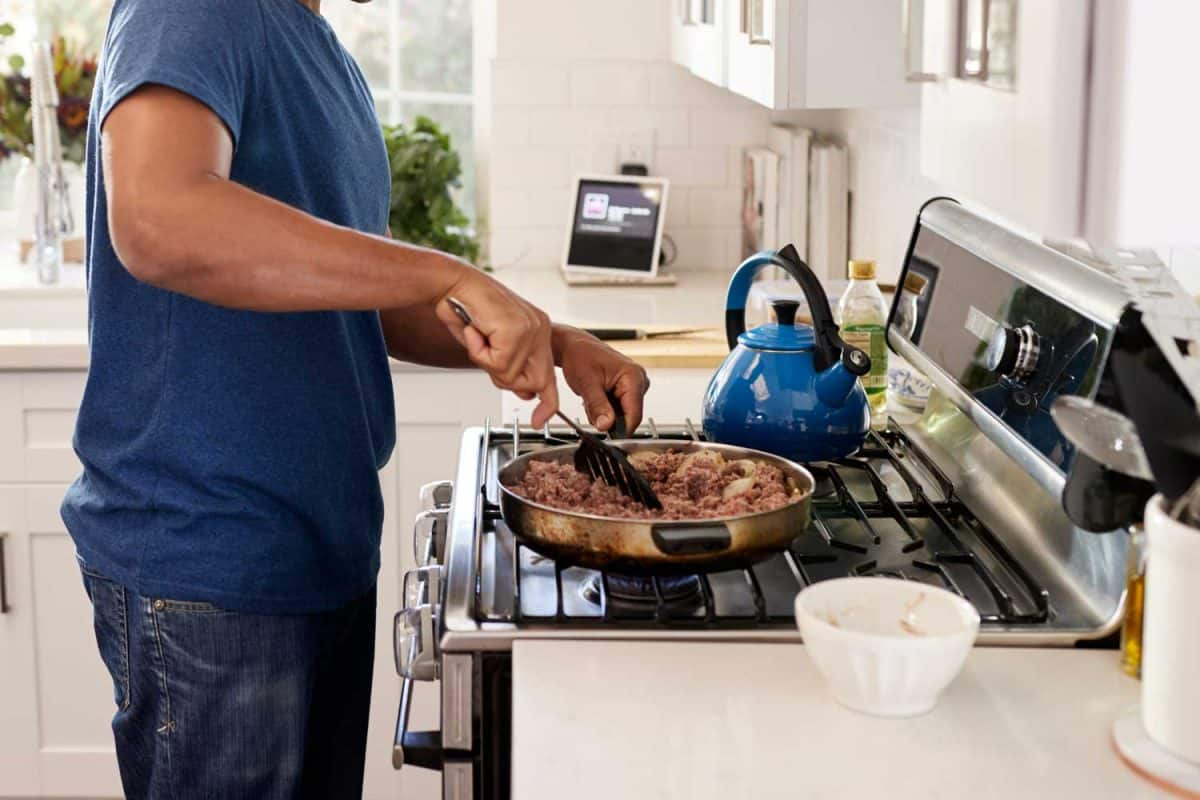 Young adult man standing in the kitchen cooking on the hob, using a spatula and frying pan