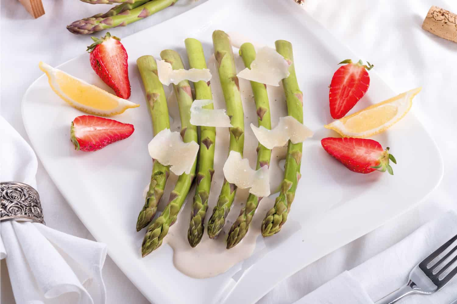Blanched asparagus garnished with sliced strawberry and lemon