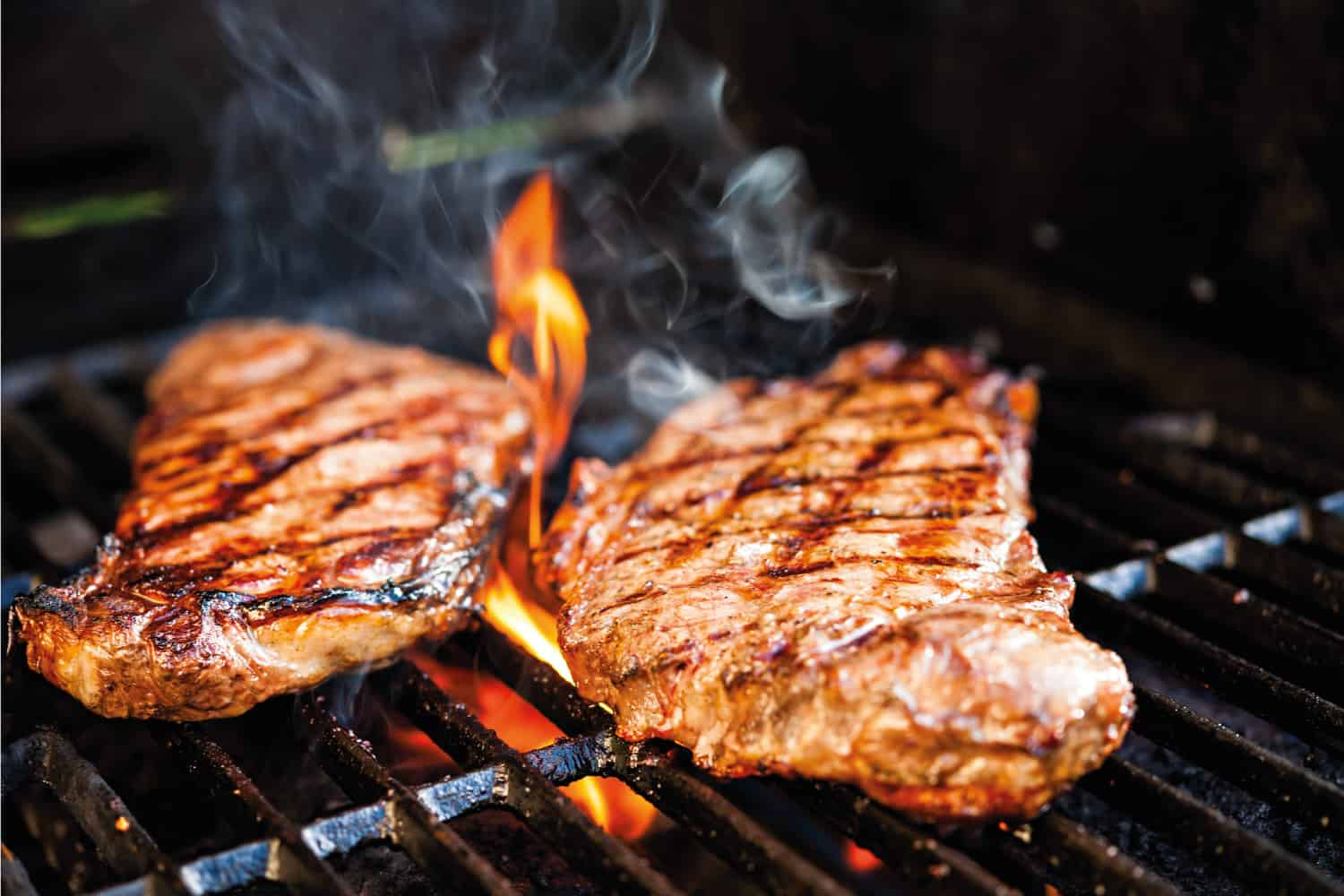 Grilling steak on a barbecue grill