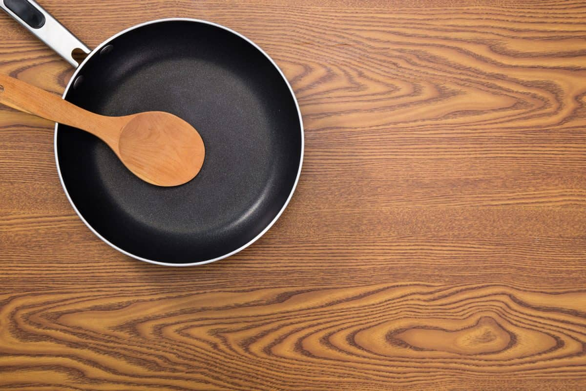 non stick frying pans on wooden background, How To Make Food Not Stick To Pan Without Oil