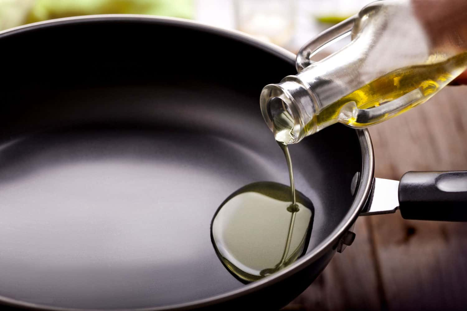 Pouring cooking oil from a glass bottle into a frying pan