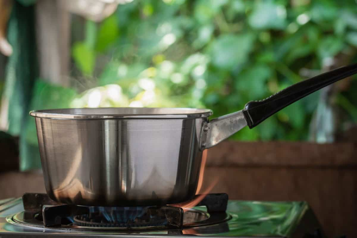 steel saucepan on the gas stove with burning in kitchen, Can You Boil Water In A Saucepan