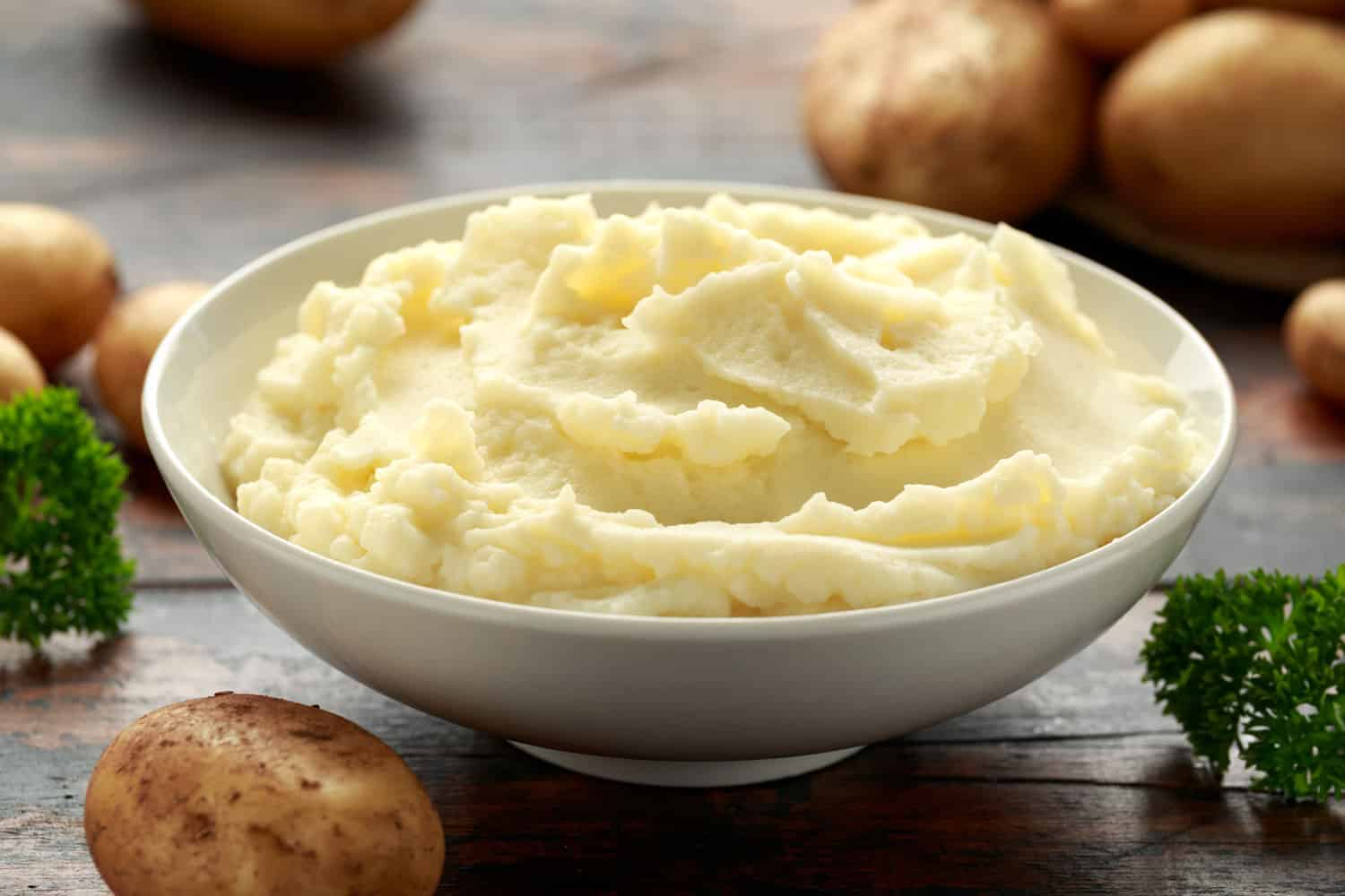 A delicious dish of mashed potatoes with unpeeled potatoes on the background