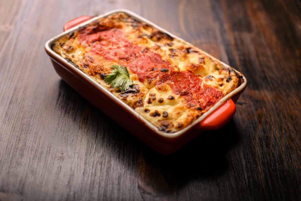 A freshly baked pot of lasagna on a red ceramic container, How Long Do You Let a Lasagna Sit?