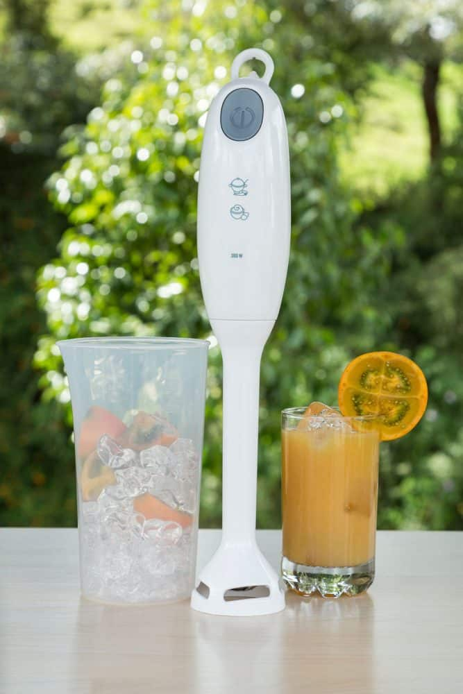 A glass of ice and a hand blender on a table