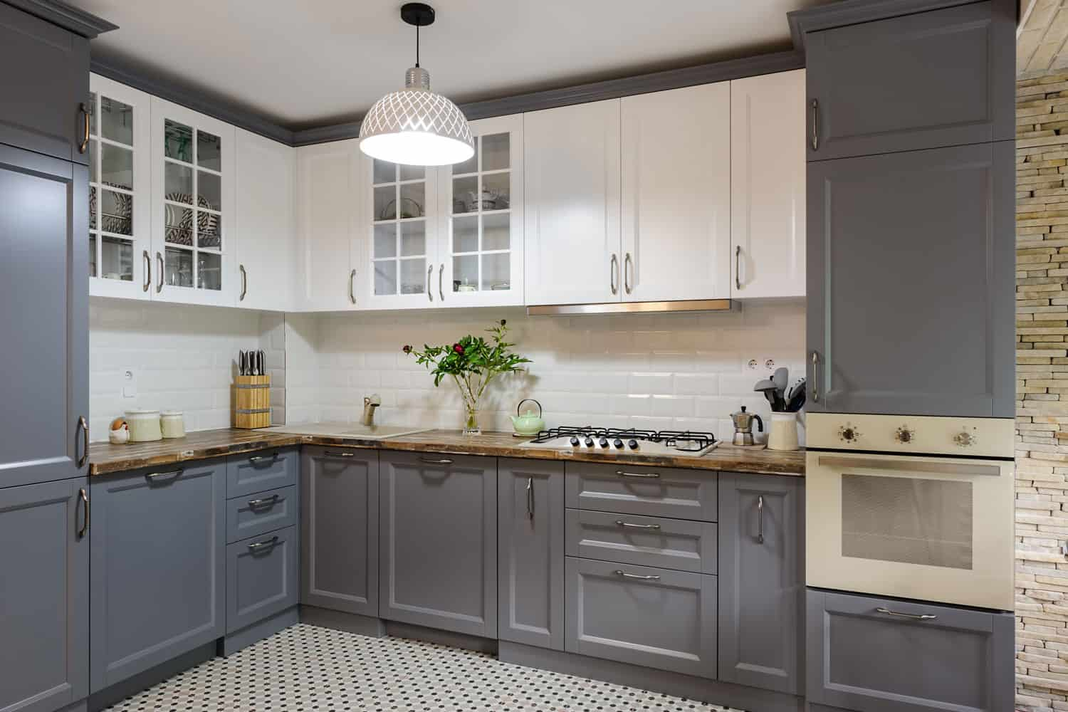 A modern gray themed kitchen area with gray cabinets, white paneled upper cabinets, and a white tiled backsplash, 5 Ways To Waterproof Cabinets Under The Kitchen Sink