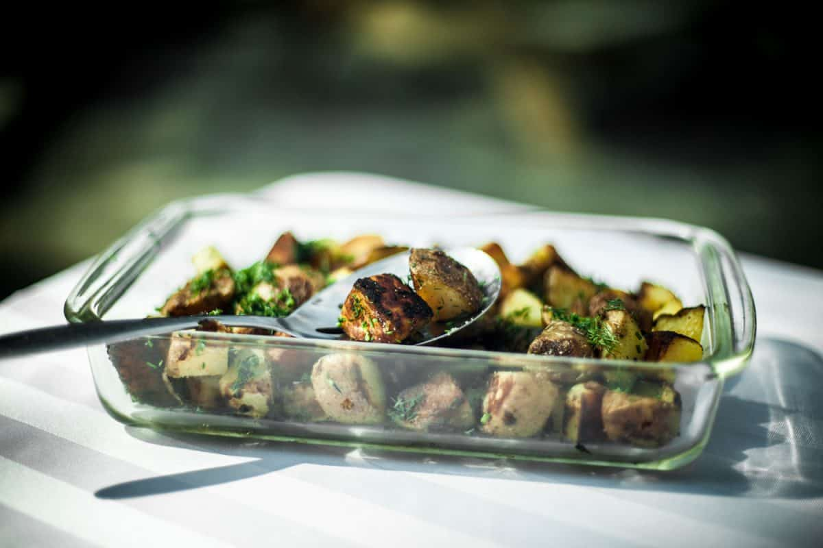 A pyrex glass platter with roasted potatoes inside it garnished with minced dill