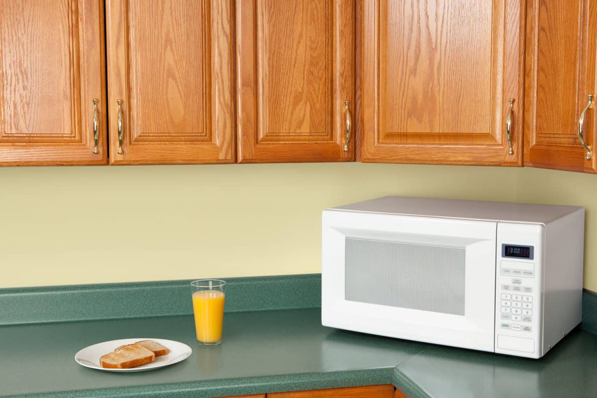 A white microwave above a green countertop