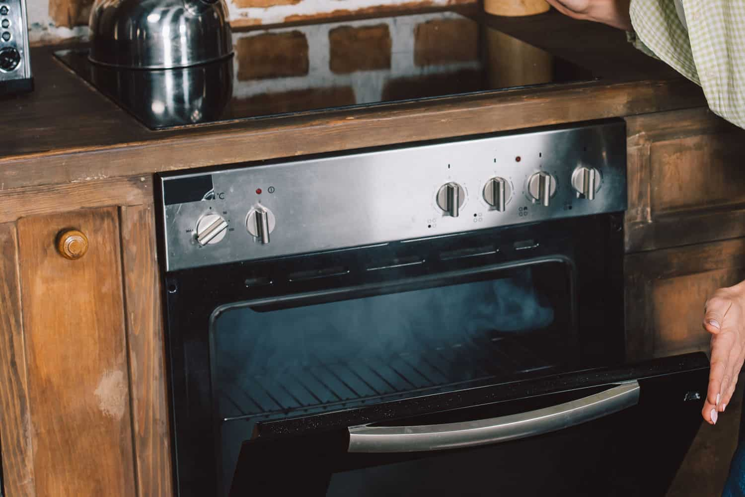 A woman opening her smoking oven
