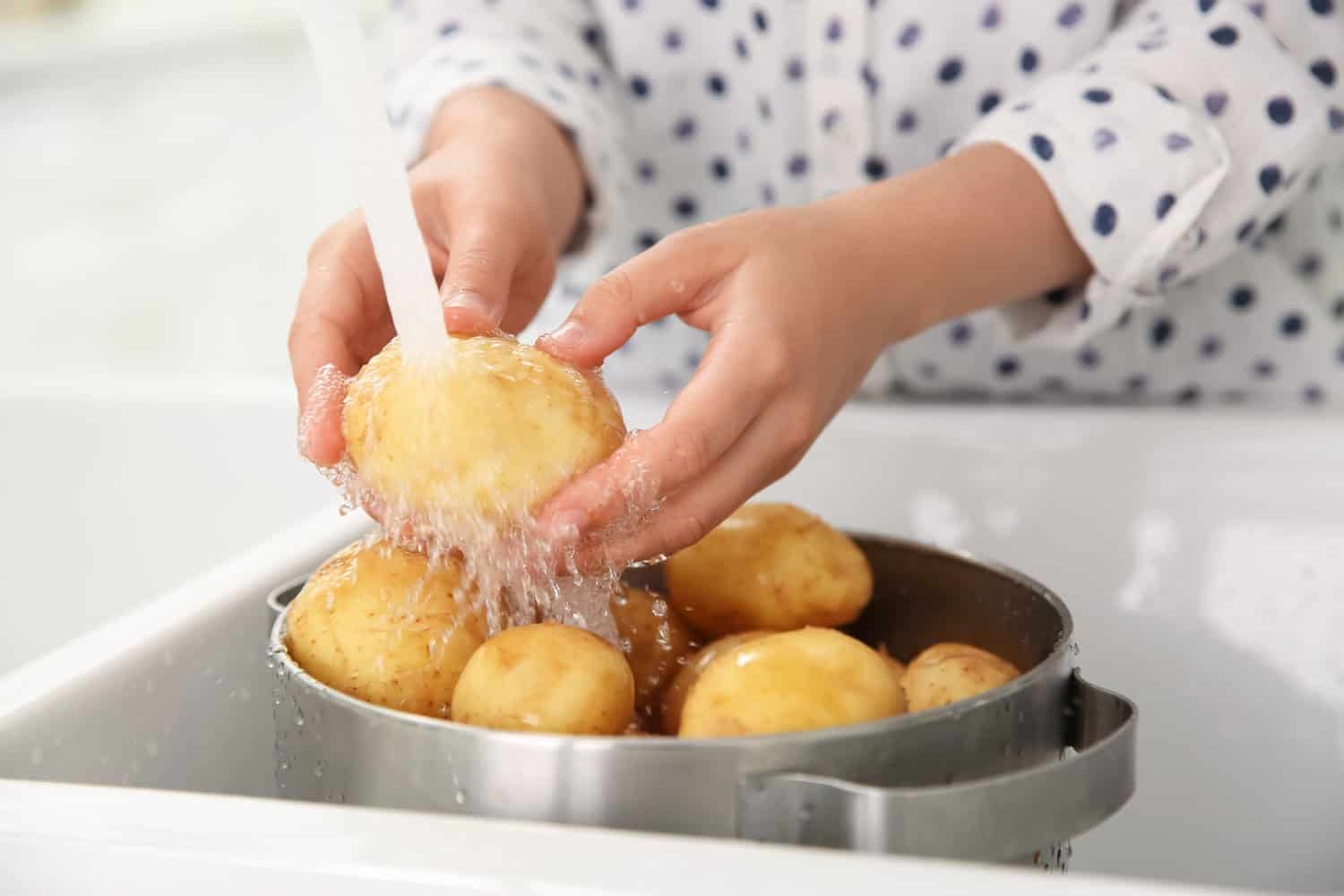 A woman washing freshly peeled potatoes on her kitchen sink