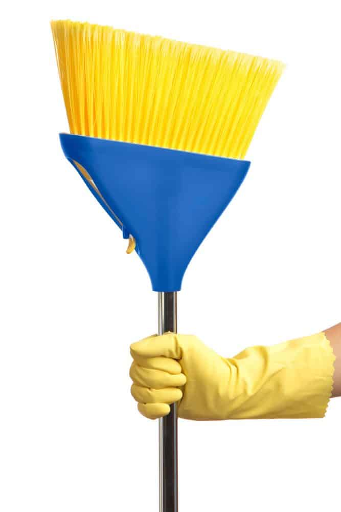A woman wearing yellow gloves and a blue plastic yellow brush broom stick