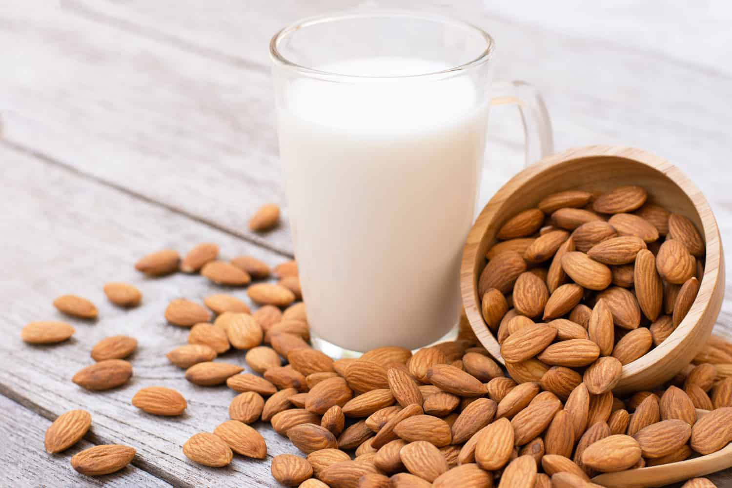 Almonds and almond milk on a wooden table