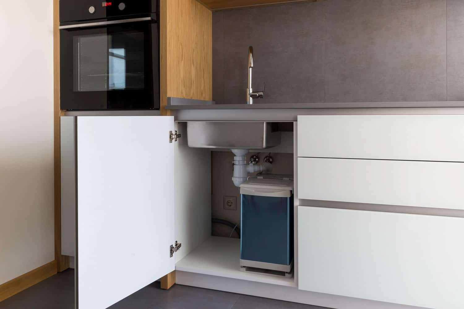 An opened kitchen cabinet with a kitchen sink underneath