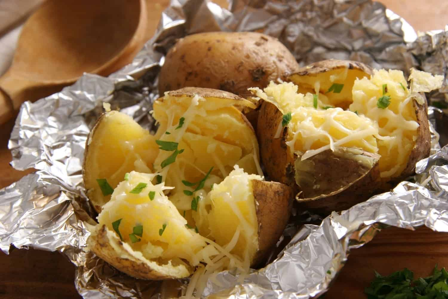 Baked potatoes with butter and cheese.
