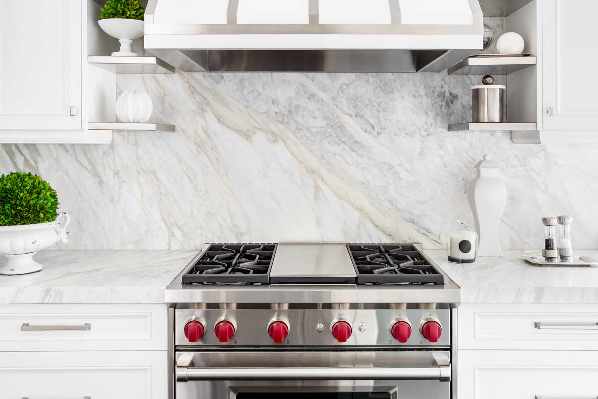 Bright classic white kitchen with gas range and marble backsplash, How Much Space Should There Be Between The Range And Wall?