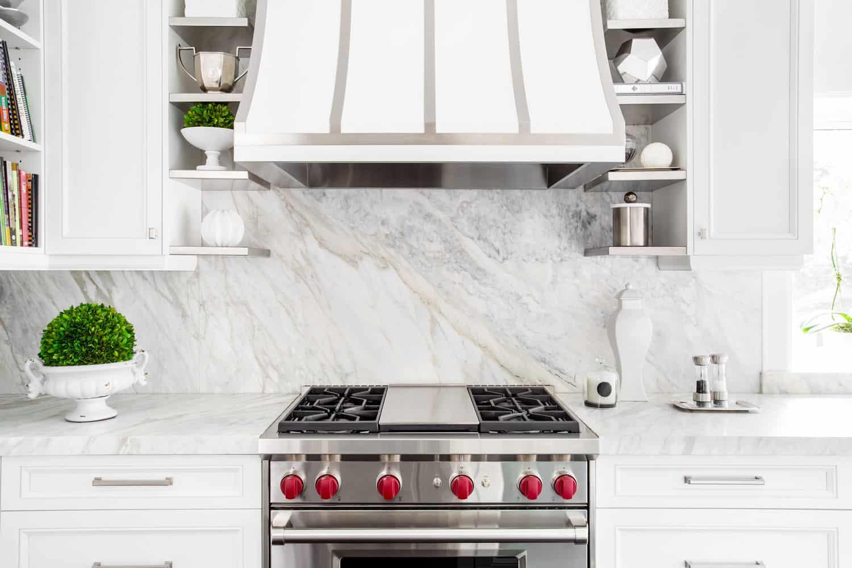 Bright horizontal image of classic white kitchen, with gas range and marble backsplash