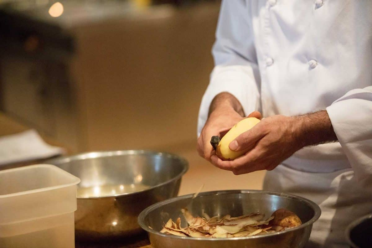 Chef peeling potatoes in commercial kitchen