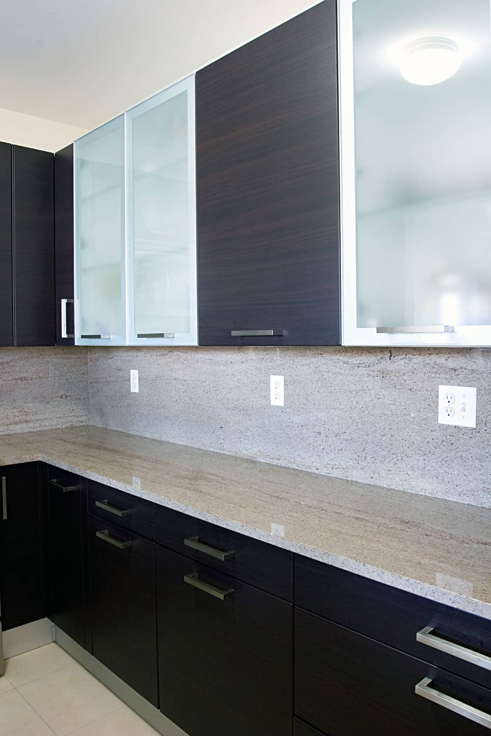 Clear wooden and glass cabinet upper doors and dotted kitchen backsplash