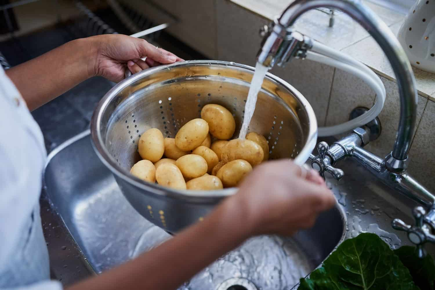 Cropped shot of a woman rinsing potatoes in a kitchen sink at home