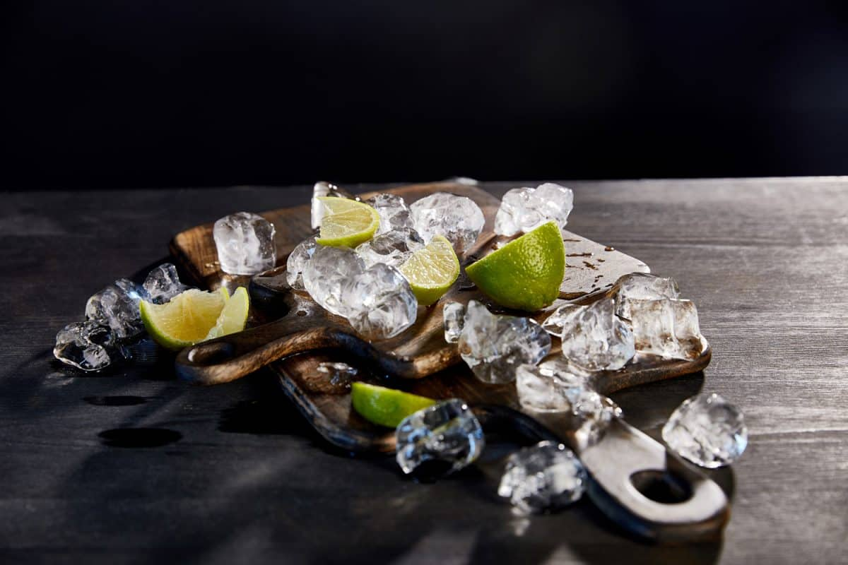 Crushed ice with sliced lemons on a wooden chopping board