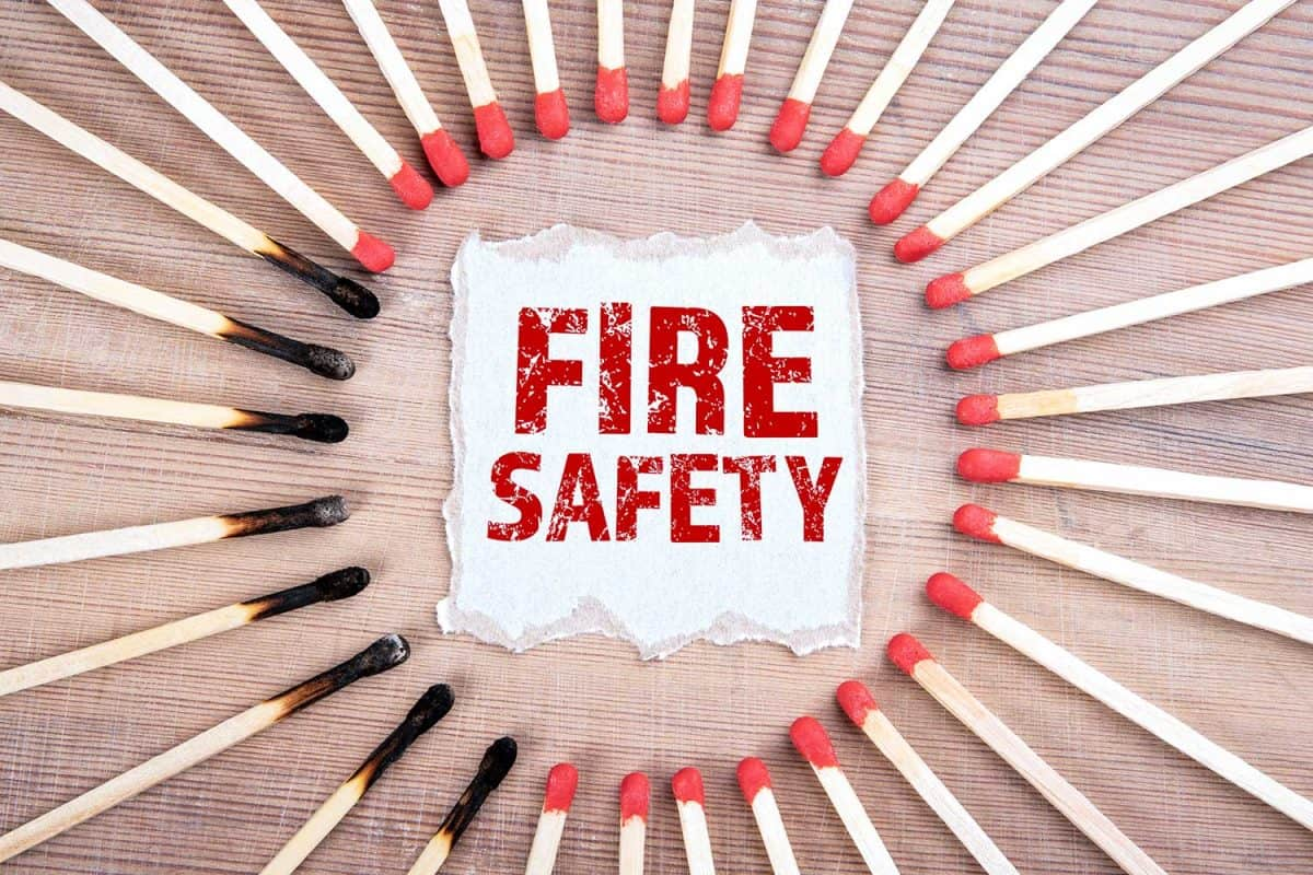 Fire safety sign surrounded by burned matches on wood texture background