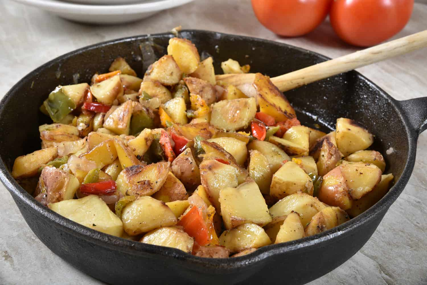 Gourmet roasted potato wedges in a cast iron skillet with bell peppers and onion